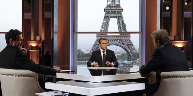 French President Emmanuel Macron poses on the TV set before an interview with RMC-BFM journalist Jean-Jacques Bourdin and Mediapart investigative website journalist Edwy Plenel, at the Theatre National de Chaillot across from the Eiffel Tower in Paris